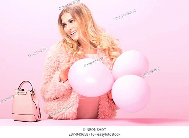 High fashion blonde woman posing in studio on pink pastel background, wearing pink clothes. Portrait of beautiful sexy girl holding balloons