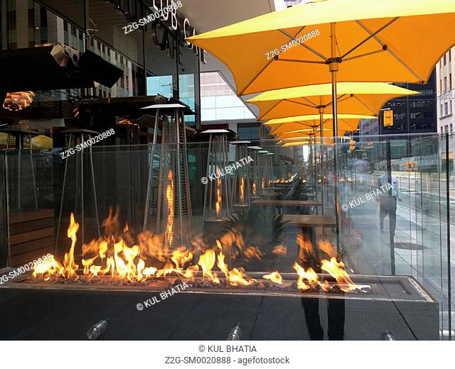 Gas flames heat up the outdoor seating area of a restaurant in cold and wet weather on a trendy street in Toronto, Canada