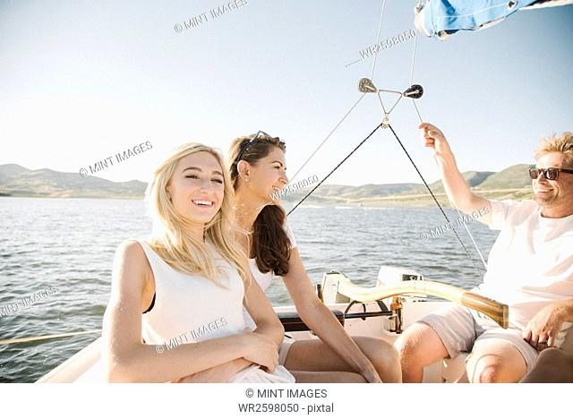 Man, woman and their blond teenage daughter on a sail boat