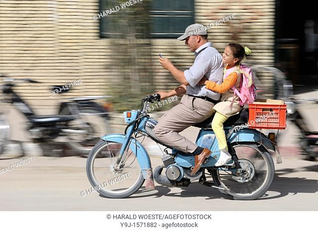 Africa, Tunisia, Tozeur  Tunisian father and doughter on moped while using mobile phone