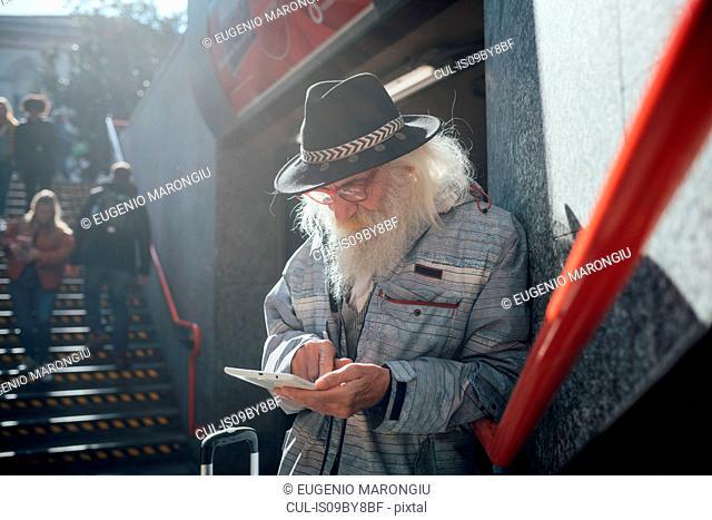 Senior man using digital tablet at entrance to subway, Milano, Lombardia, Italy