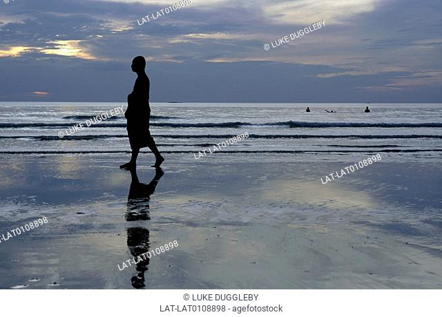 National park. Beach. Thai Buddhist monk in long robe. Walking on sand. Sunset. Low light. Silhouette