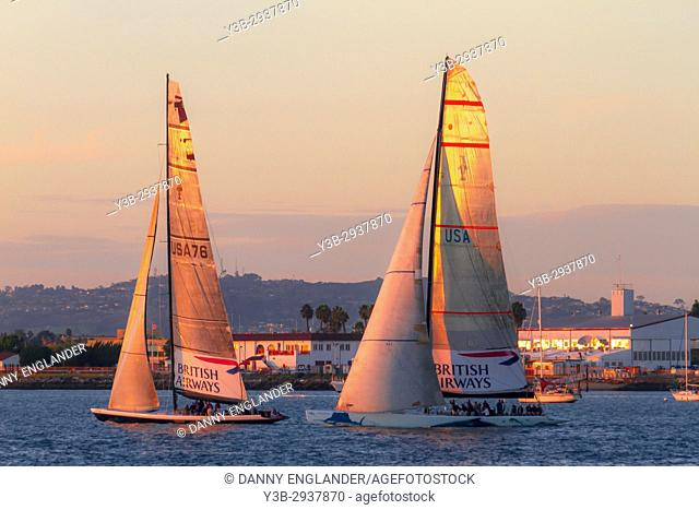 Two sailboats cruise San Diego Bay close to sunset in Southern California