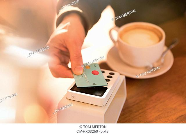 Close up man paying for cappuccino with credit card contactless payment in cafe