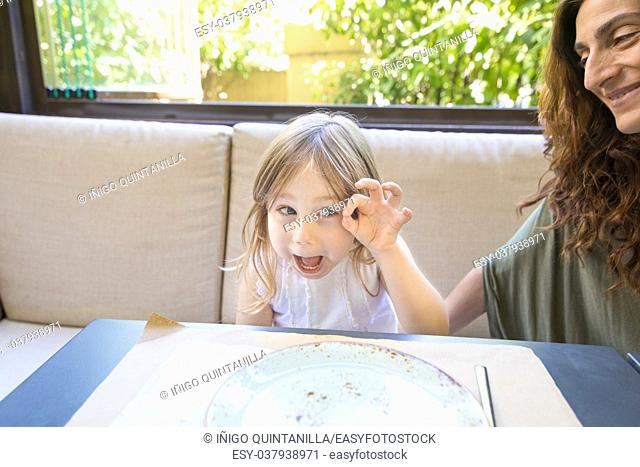 Funny expression and gesture. Four years age blonde happy girl teasing and grimacing next to woman mother smiling sitting in restaurant