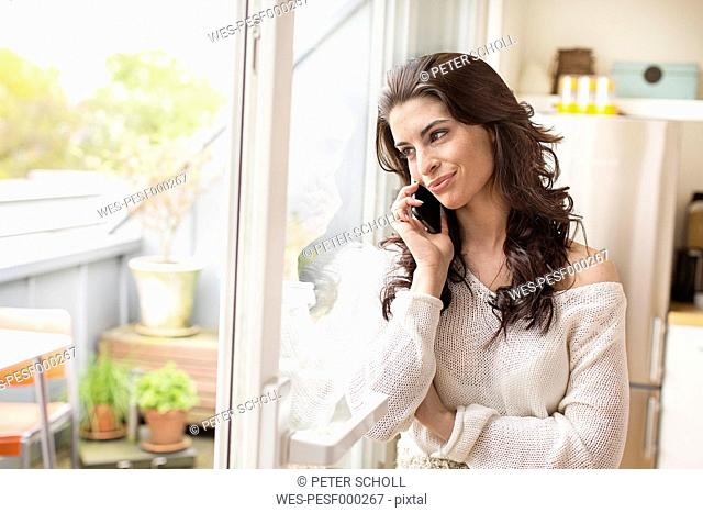 Smiling young woman on cell phone at the window