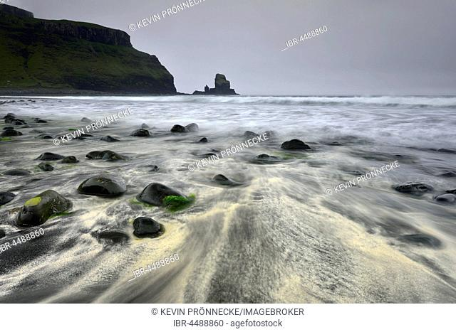 Stones in the sand on the beach of Talisker Bay, cliffs and rocks, Isle of Skye, Scotland, United Kingdom