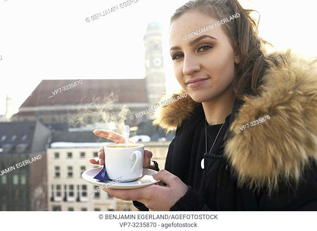 young woman with warm steaming coffee cup outdoors in city next to touristic attraction Frauenkirche, Marienkirche, in Munich, Germany