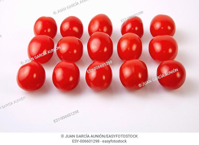 Red shiny cherry tomatoes. Isolated over white background