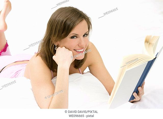 Beautiful Caucasian woman in bed reading a book