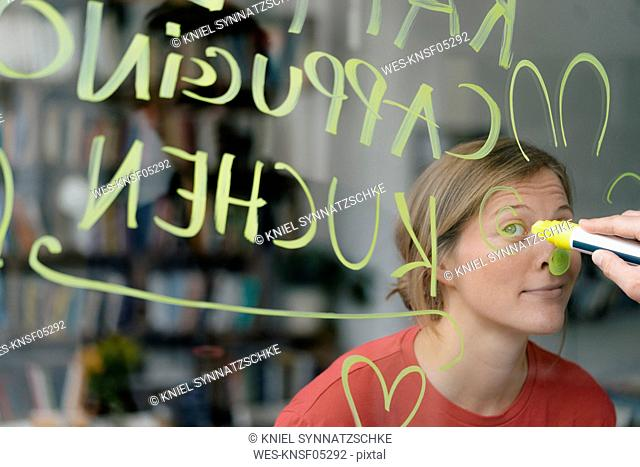 Portrait of young woman behind windowpane in a cafe with hand writing