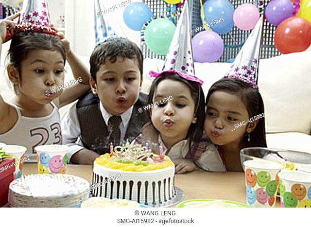 Children celebrating birthday, blowing candles on cake