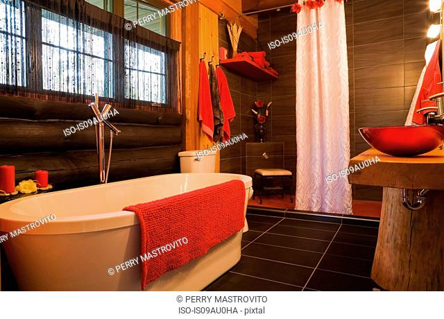 Modern bathroom in log cabin, red accessories