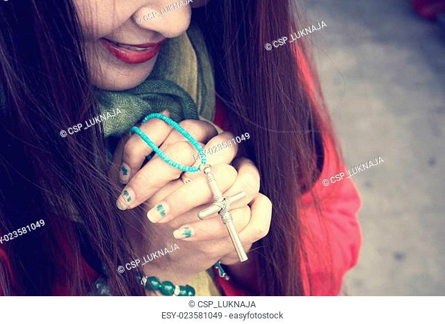 Woman hands praying with cross