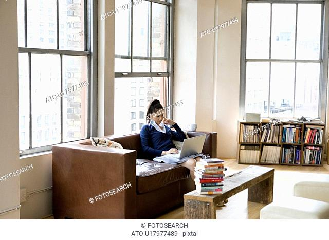 A Woman Sitting on Sofa, Looking at Laptop