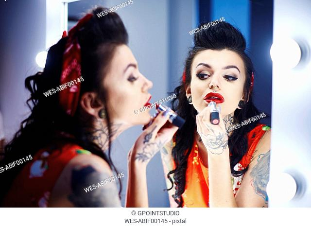 Mirror image of tattooed woman applying red lipstick