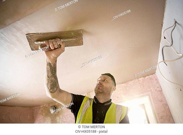 Construction worker with tattoo plastering ceiling