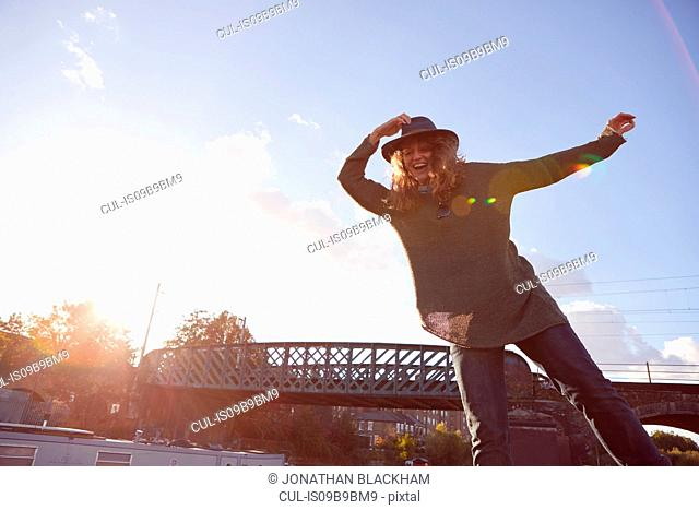 Woman balancing by canal, bridge in background