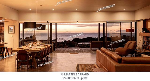 Home showcase interior overlooking ocean at sunset