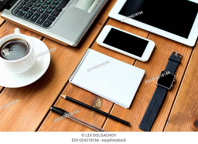 education, business and technology concept - close up of on laptop computer, tablet pc, notebook and smartphone on wooden table