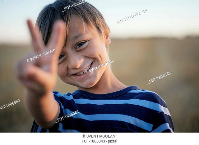 Portrait smiling, carefree boy gesturing peace sign