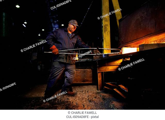 Forge worker removes red hot steel billet from furnace for forging into crank shaft