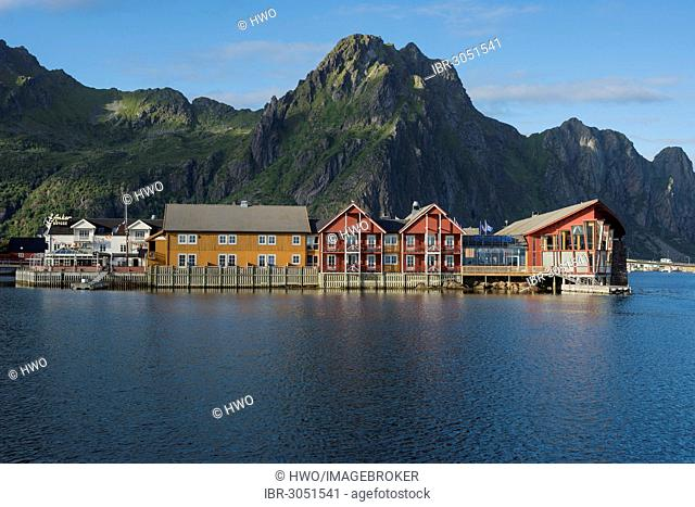 Wooden houses at the harbor entrance of Svolvaer, mountain range at back
