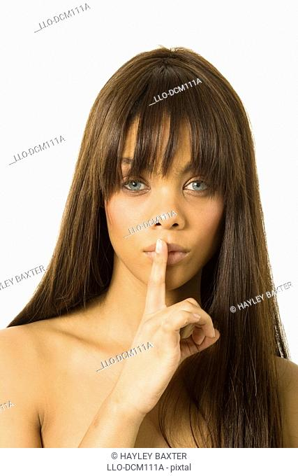 Studio shot of Young girl holding finger over mouth gesturing silence