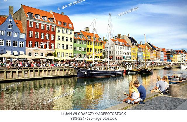 Turists resting at Nyhavn Canal, Copenhagen, Denmark