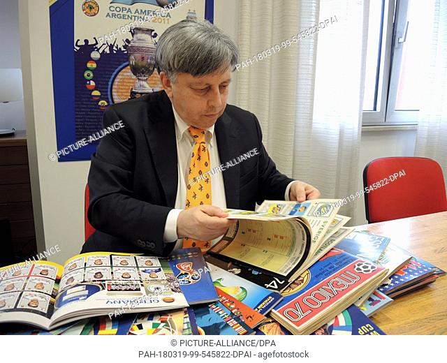 12 March 2018, Italy, Modena: Fabrizio Melegari, director of the Panini editorial staff, sits in front of a stack of sticker sheets