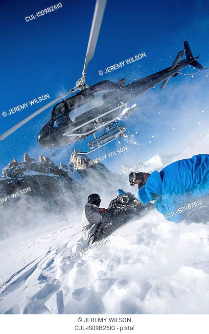 Helicopter leaving male snowboarders on mountain, Trient, Swiss Alps, Switzerland