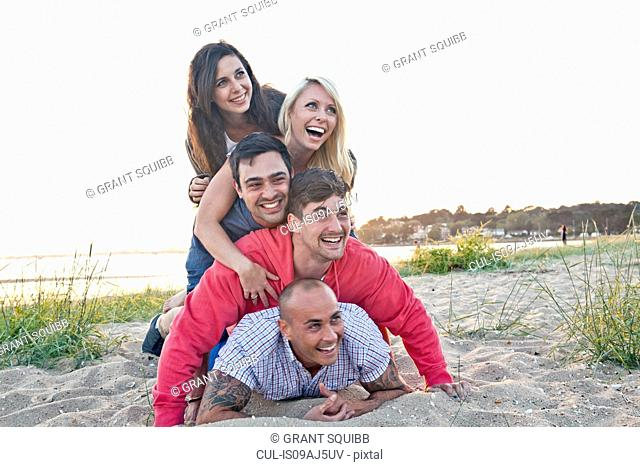 Group of friends making human pile on beach