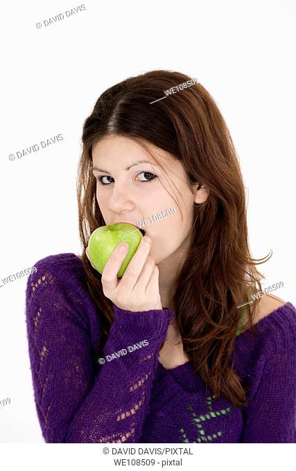 Teenage girl eating a green apple