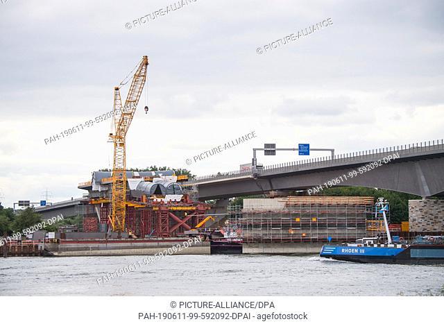 08 June 2019, Hessen, Wiesbaden: An inland waterway vessel passes the bridge construction site. The Schiersteiner Bridge connects the Hessian and...