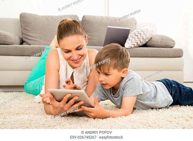 Smiling Mother And Son Lying On Carpet Using Digital Tablet