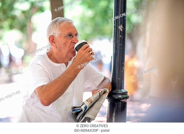 Senior man drinking takeaway coffee in city