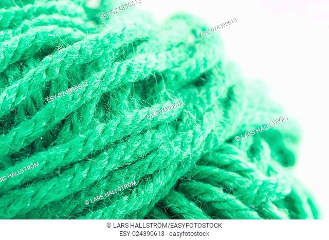 Ball of yarn in close up. The needlework thread is green. Concept of traditional hobby and a creative leisure activity