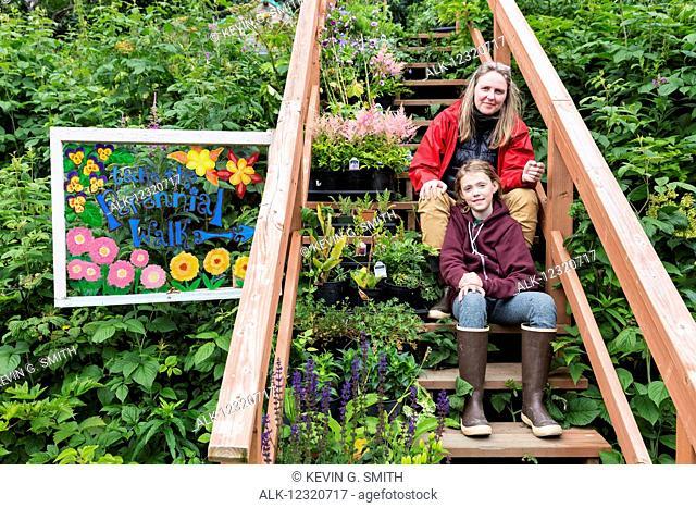 Mother and daughter sit on steps among a lush garden, Seldovia, Southcentral Alaska, USA