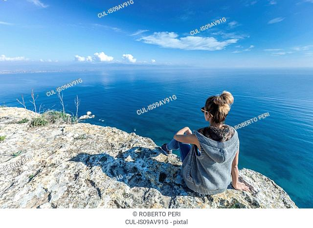 Rear view of young woman sitting on cliff looking out at view of ocean, Cagliari, Sardinia, Italy