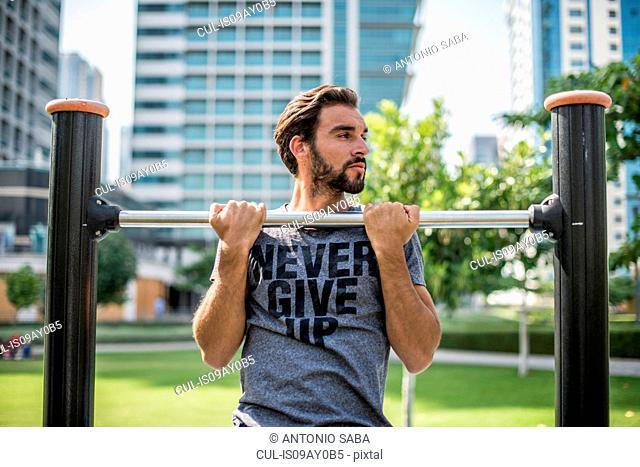 Young man doing pull ups on park exercise equipment, Dubai, United Arab Emirates