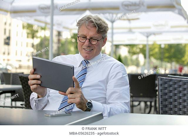 Businessman with iPad is sitting on the table in a street restaurant