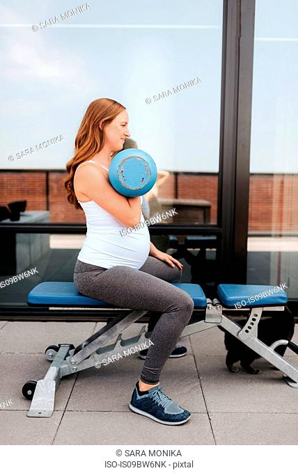 Pregnant woman using weights on balcony
