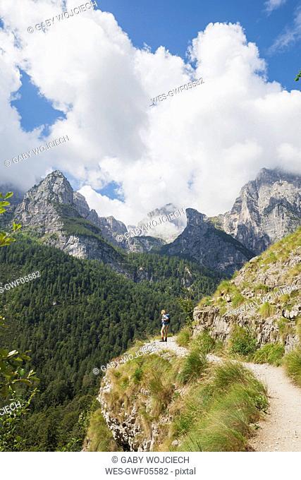 Italy, Trentino, Brenta Dolomites, Parco Naturale Adamello Brenta, woman enjoying mountain scenery on trail along Croz dell' Altissimo