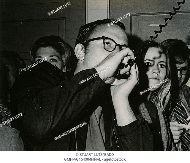 Close-up of a student speaking into the microphone of a bullhorn loudspeaker during an anti Vietnam War student sit-in protest at North Carolina State...