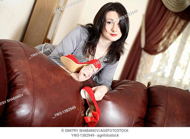 Caucasian woman with shoes in hands