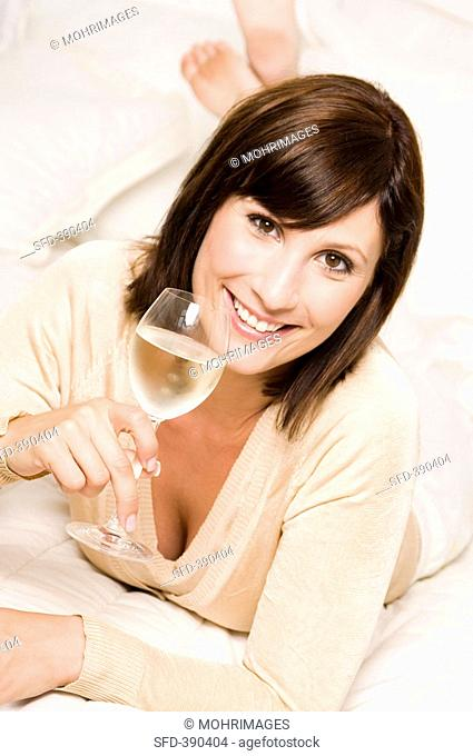Woman with a glass of white wine lying on bed
