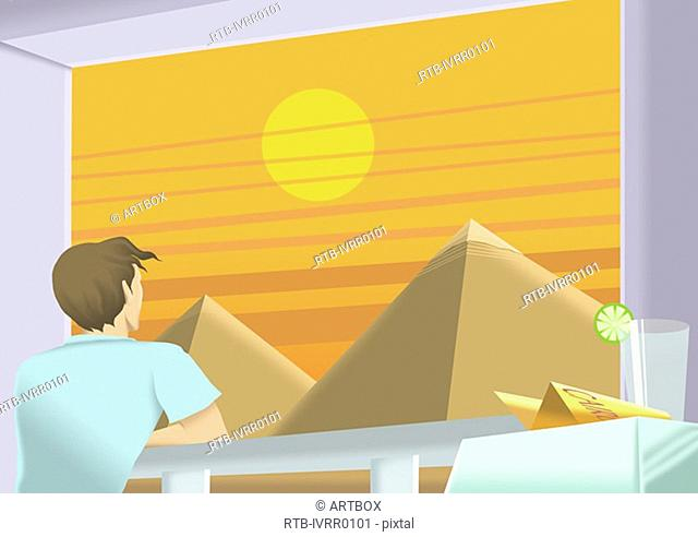 Young man looking at pyramids through a window