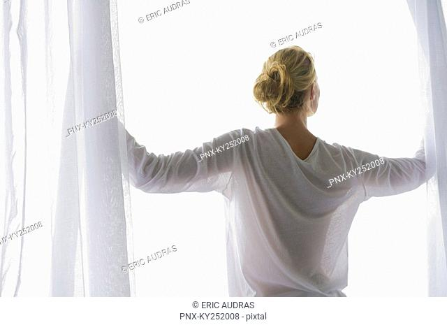 Rear view of a woman opening the curtain of balcony