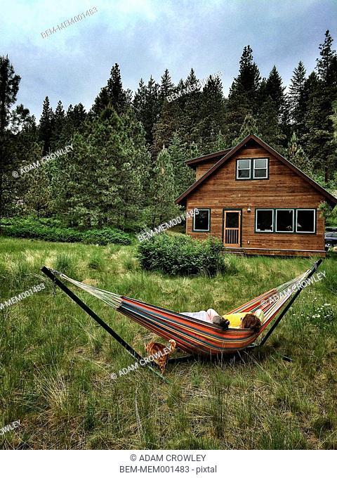 Children relaxing in hammock in rural landscape
