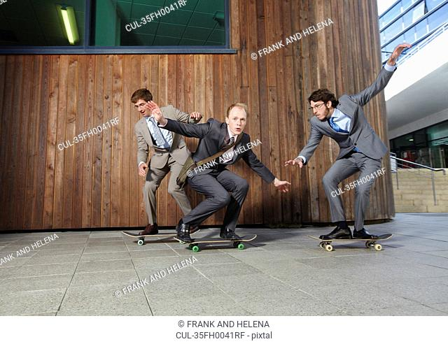 Businessmen riding skateboards